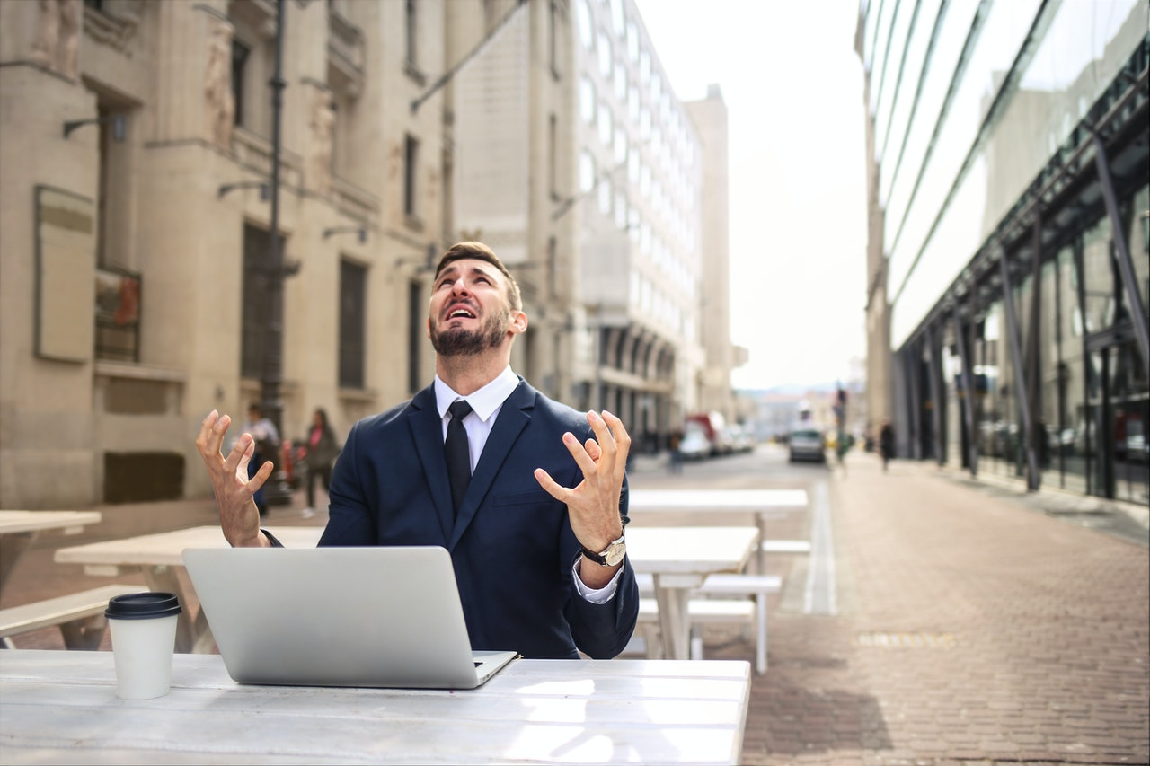 man working on a laptop angrily