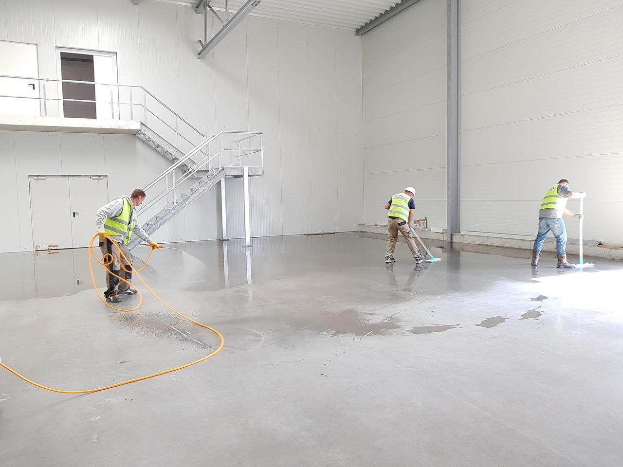 three men cleaning the floor