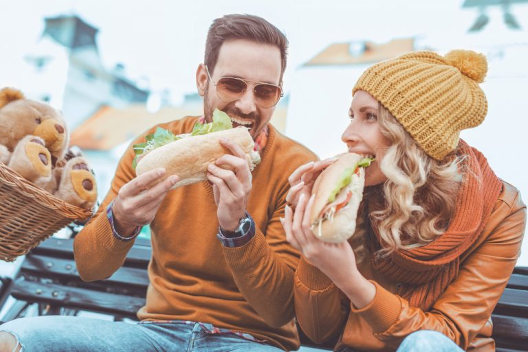 man and woman eating subs