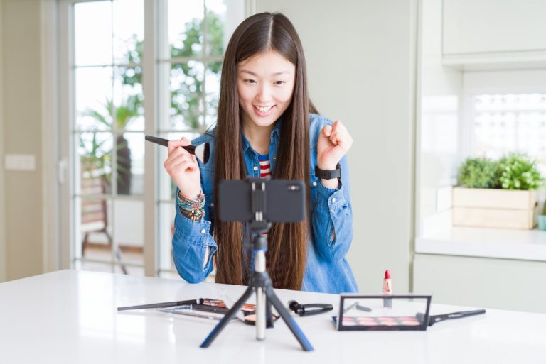 girl broadcasting in front her camera holding a makeup brush