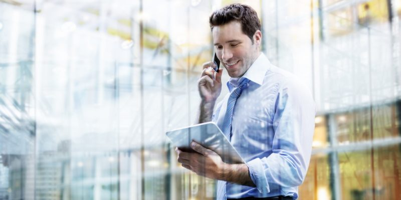 businessman holding an ipad while on phone